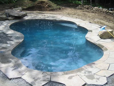 freeform pool with slate coping under construction